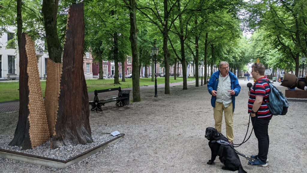 Midden op de Laan van de Lange Voorhout bespreken Ferry en Louis het beeld Triomf